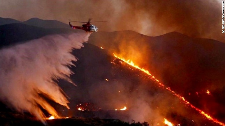 An Los Angeles County Fire Department Air Ops Chopper drops water over the Sand Fire.