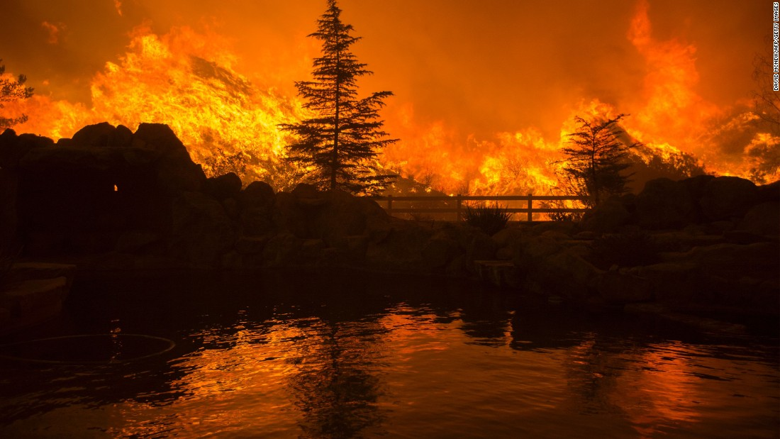 """Flames from the Sand Fire are reflected in a backyard swimming pool near Santa Clarita, California, on Saturday, July 23. The wildfire <a href=""""http://www.cnn.com/2016/07/26/us/california-wildfires/"""" target=""""_blank"""">forced thousands from their homes</a> on the edge of Los Angeles."""