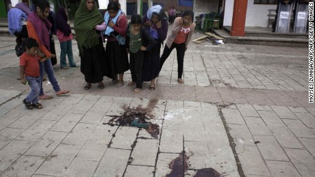 Indigenous people look at blood on the pavement in the site where San Juan Chamula's Mayor Domingo Lopez Gonzalez was killed during a protest in San Juan Chamula, Chiapas state, Mexico on July 23, 2016. A mayor and two local officials were among five people shot dead during a protest on Saturday in a southern Mexico town with a history of religious and political conflict. / AFP / MOYSES ZUÑIGA        (Photo credit should read MOYSES ZUNIGA/AFP/Getty Images)