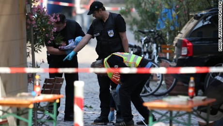 Police officers conduct an investigation on Monday, July 25, following a suicide bombing in Ansbach, Germany the evening before. A man who has been identified as a Syria who had been denied asylum in Germany detonated a device in his backpack in front of a restaurant, killing himself and injuring 12 others. Around 2,500 people were evacuated from a nearby music festival venue where the man had earlier been denied entry.