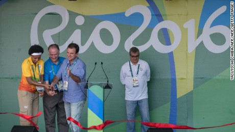 Rio de Janeiro Mayor Eduardo Paes (right, blue shirt) helps cut the ribbon during the opening ceremony of the Olympic Village on July 24.