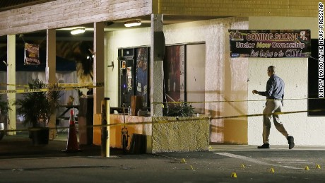 An investigator walks near the scene of a fatal shooting at Club Blu nightclub in Fort Myers, Florida on Monday, July 25.