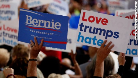 """A delegate holds a sign in support of Sen. Bernie Sanders (I-VT) and another that reads """"Love trumps hate"""" on the first day of the Democratic National Convention at the Wells Fargo Center, July 25, 2016 in Philadelphia, Pennsylvania. An estimated 50,000 people are expected in Philadelphia, including hundreds of protesters and members of the media. The four-day Democratic National Convention kicked off July 25."""