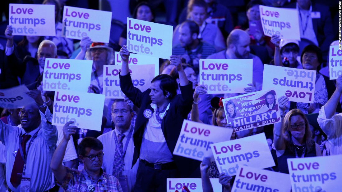"""Delegates hold signs reading """"Love trumps hate"""" on Monday."""