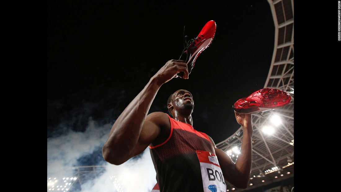 Jamaica's Usain Bolt holds out his spikes as he interacts with spectators after winning the men's 200m at the IAAF Diamond League Anniversary Games athletics meeting at the Queen Elizabeth Olympic Park stadium in Stratford, east London on July 22, 2016.