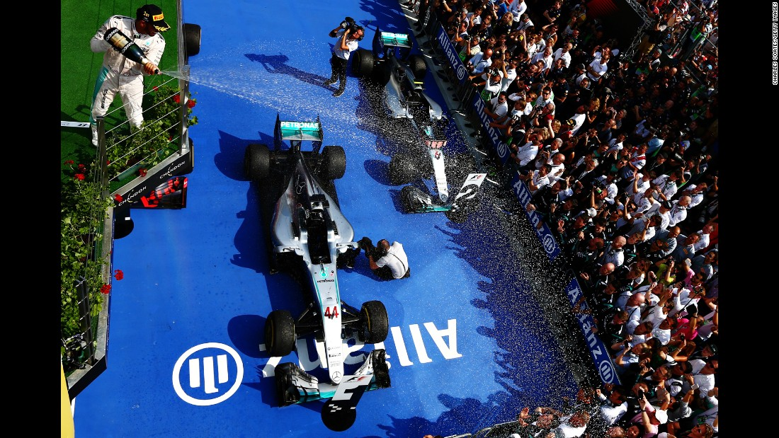 """Formula One driver Lewis Hamilton celebrates on the podium after <a href=""""http://www.cnn.com/2016/07/24/motorsport/hungarian-grand-prix-lewis-hamilton/index.html"""" target=""""_blank"""">winning the Hungary Grand Prix</a> on Sunday, July 24. It was the third straight victory for Hamilton, the 2015 champion, and he is now in first place in the overall standings."""