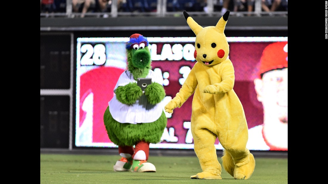 """Even the Phillie Phanatic has <a href=""""http://www.cnn.com/2016/07/11/health/pokemon-go-guide-trnd/index.html"""" target=""""_blank"""">Pokemon fever.</a> The iconic mascot, left, tries to capture Pikachu during a Philadelphia Phillies game on Tuesday, July 19."""