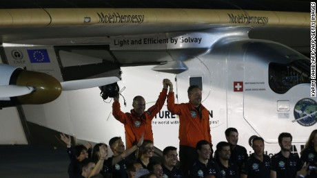 Bertrand Piccard (R) and Andre Borschberg (L), pilots of the solar powered Solar Impulse 2 aircraft, are greeted upon arrival at Al Batin Airport in Abu Dabi to complete its world tour flight on July 26, 2016 in the United Arab Emirates. Solar Impulse 2 landed in the UAE early on Tuesday, July 26, 2016, completing its epic journey to become the first sun-powered airplane to circle the globe without a drop of fuel. / AFP PHOTO / KARIM SAHIBKARIM SAHIB/AFP/Getty Images