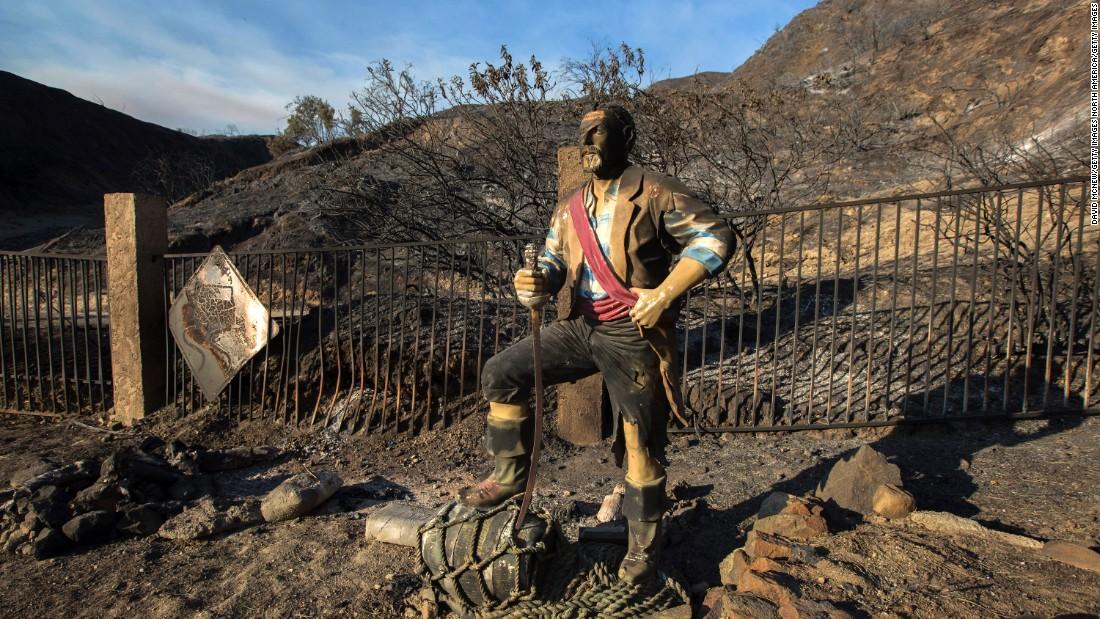 A burned pirate sculpture stands in the charred landscape in Santa Clarita.