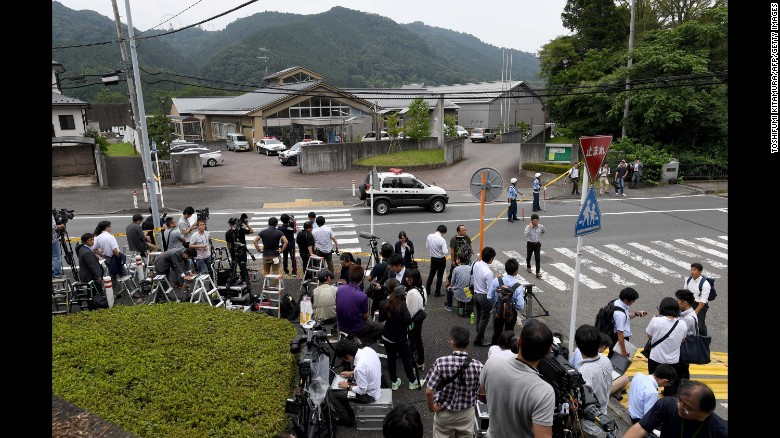 Journalists gather at the main gate of the Tsukui Yamayuri En care center