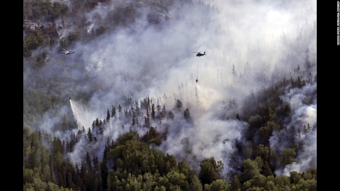 Helicopters with the Alaska Army National Guard and Alaska's Division of Forestry dump water onto the McHugh Creek wildfire near Anchorage, Alaska, on Wednesday, July 20.