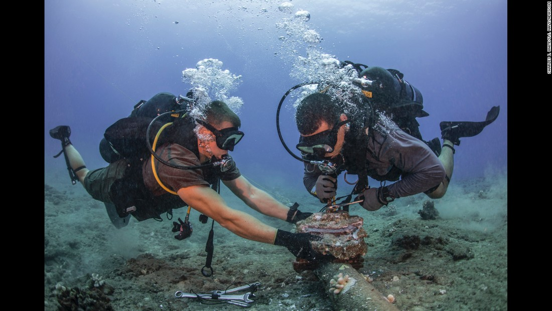 U.S. Navy construction mechanic Andersen Gardner, left, and chief construction electrician Daniel Luberto remove corroded zinc anodes from an undersea cable at the Pacific Missile Range Facility in Hawaii on Tuesday, July 5.