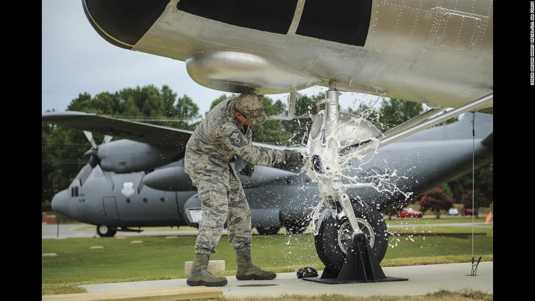 "Air Force Master Sgt. Matthew Tabor breaks a bottle to christen an H-21B helicopter while wearing the ""tiger-stripe"" Airman Battle Uniform in July."