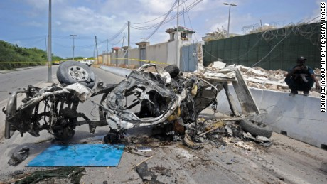 Somali soldiers stands on guard next to the wreckage of a car bomb outside the UN's office in Mogadishu on July 26, 2016.   At least 13 people were killed on July 26 in twin bombings near UN and African Union buildings adjoining Mogadishu's airport, police said, in what the jihadist Shabaab group claimed as a suicide attack.