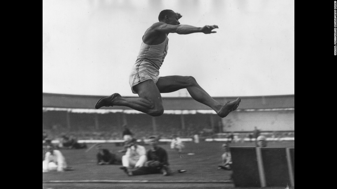 Owens takes part in a long-jump event in London in August 1936.