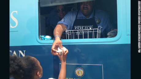 A police officer hands a frozen treat to a young girl.
