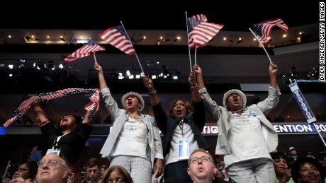Attendees wave American flags during the third day of the Democratic National Convention at the Wells Fargo Center, July 27, 2016 in Philadelphia, Pennsylvania.