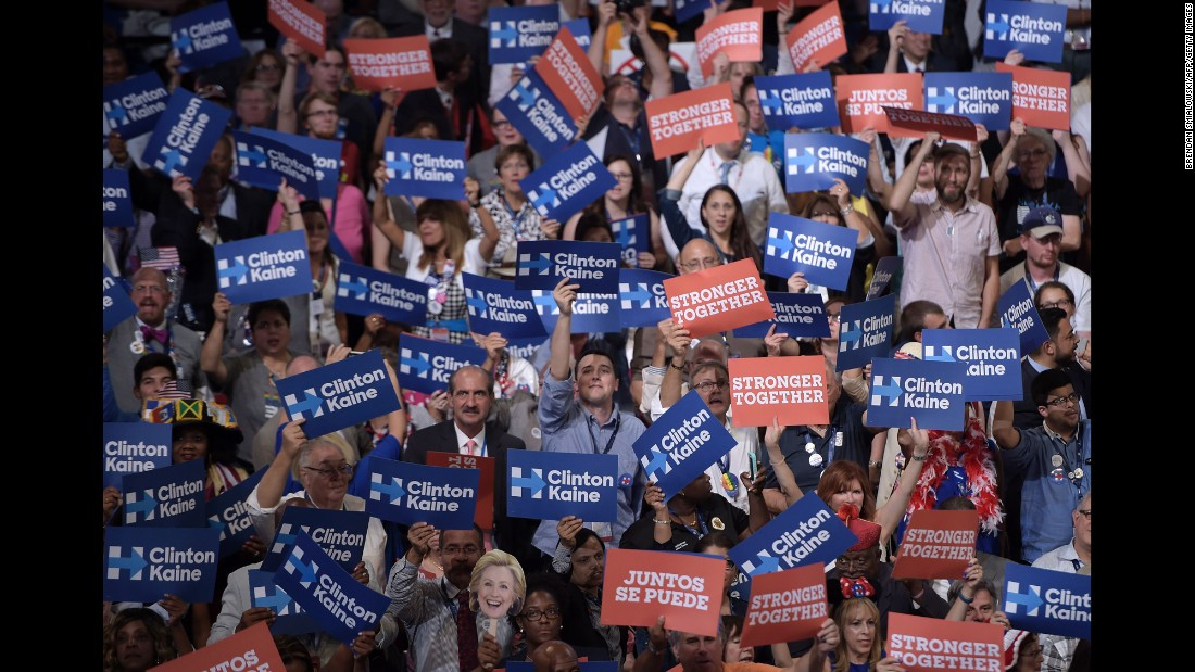 Delegates hold posters during Kaine's speech.
