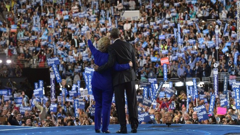 Obama and Clinton acknowledge the crowd at the Wells Fargo Center.