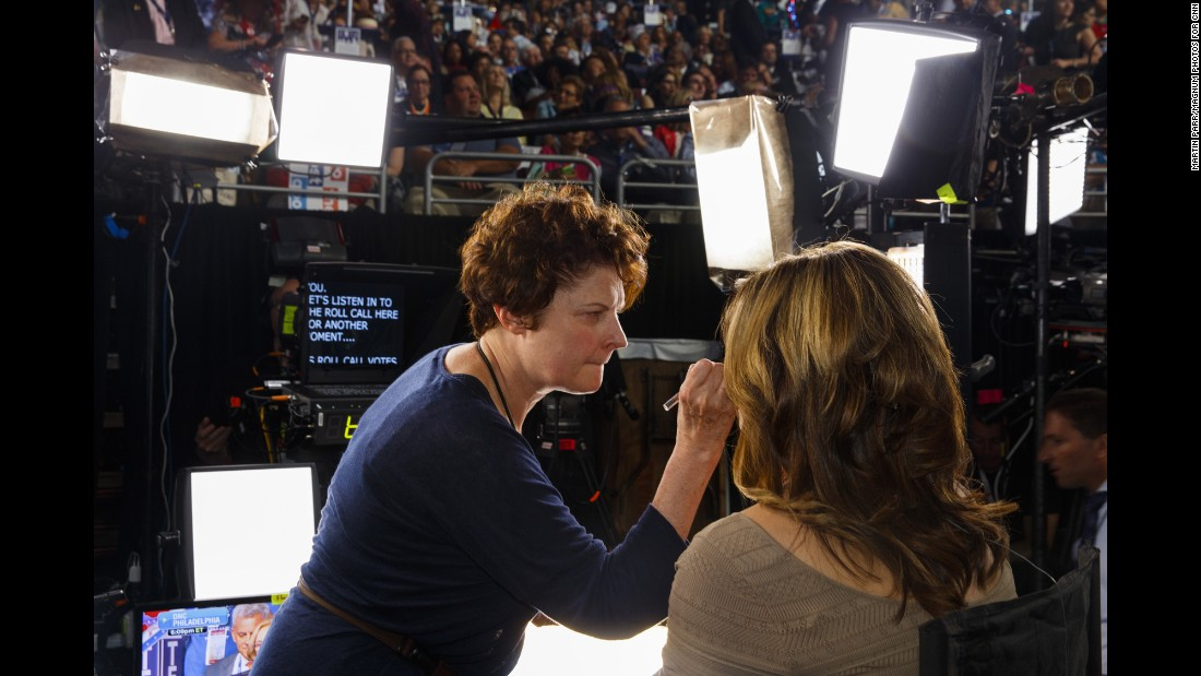A woman has her makeup touched up before going on air.
