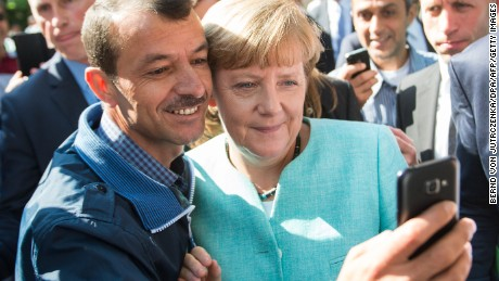 An asylum seeker takes a selfie with German Chancellor Angela Merkel during the leader's visit to refugee registration centre in Berlin on September 10, 2015.