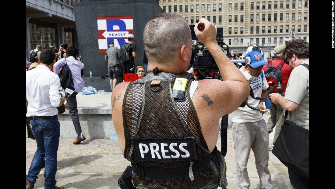 A member of the press films protesters outside City Hall.