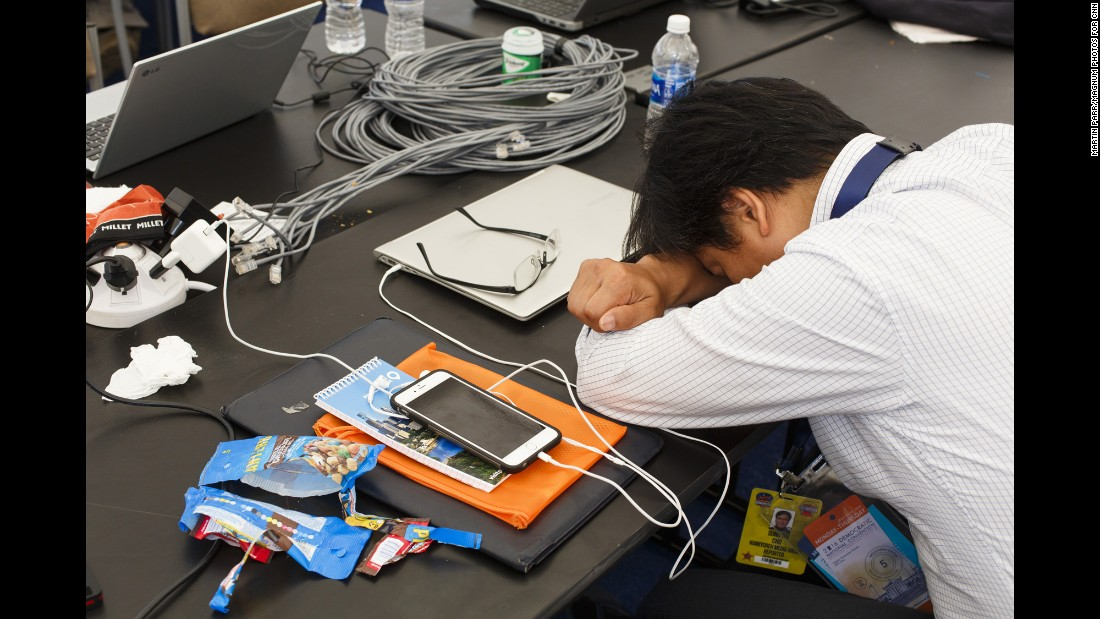 A journalist from The Hankyoreh, a South Korean newspaper, rests in the media pavilion.