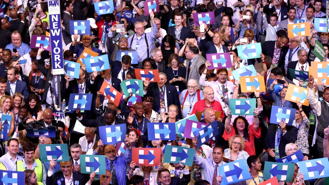 Delegates hold up signs in support of presidential nominee Hillary Clinton.