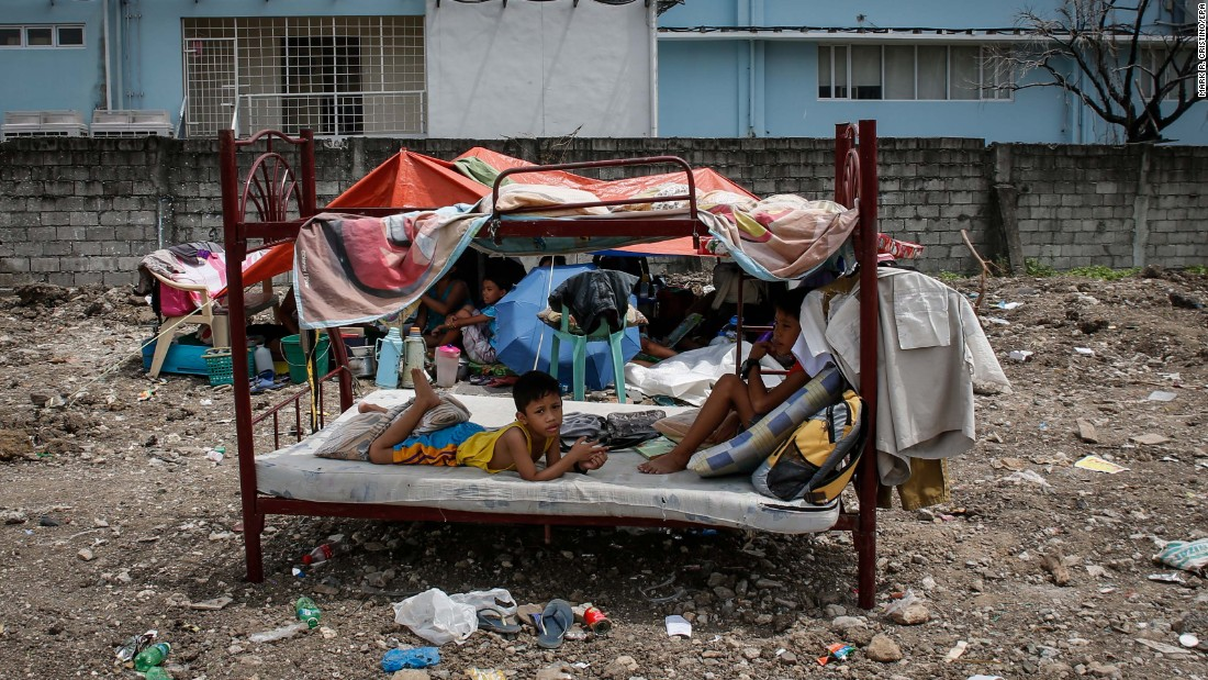 Children rest on their salvaged bed after a fire in Pasay, Philippines, on Thursday, July 28. Around 150 families were affected by the fire, and four people were killed, according to the Bureau of Fire Protection.