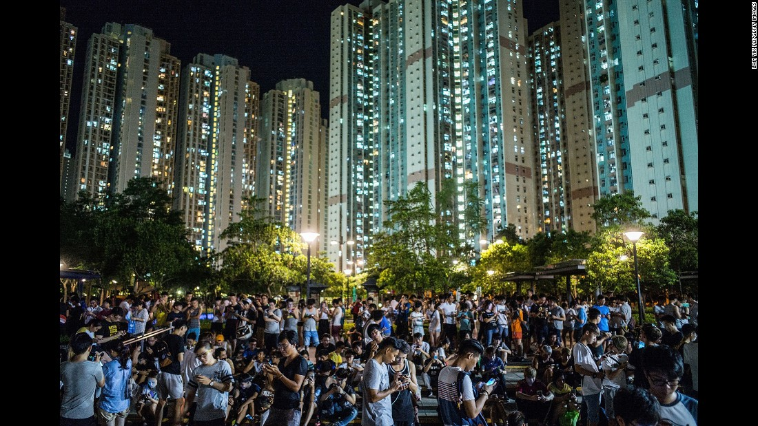 """People play the mobile game """"Pokemon Go"""" at a park in Hong Kong on Tuesday, July 26."""