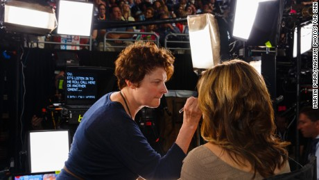 A woman has her makeup touched up before broadcasting during the roll call.