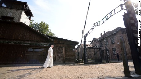 """Pope Francis walks towards the main entrance with the lettering """"Arbeit Macht Frei"""" (Work Sets You Free) at the former Nazi German Auschwitz-Birkenau death camp on July 29, 2016 in Oswiecim as part of his visit to the World Youth Days (WYD). Pope Francis is in Poland for an international Catholic youth festival with a mission to encourage openness to migrants."""