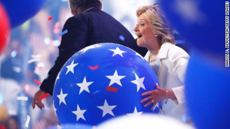 Democratic presidential candidate Hillary Clinton plays with balloons on stage at the end of the fourth day of the Democratic National Convention at the Wells Fargo Center, July 28, 2016 in Philadelphia, Pennsylvania. Democratic presidential candidate Hillary Clinton received the number of votes needed to secure the party's nomination. An estimated 50,000 people are expected in Philadelphia, including hundreds of protesters and members of the media. The four-day Democratic National Convention kicked off July 25.