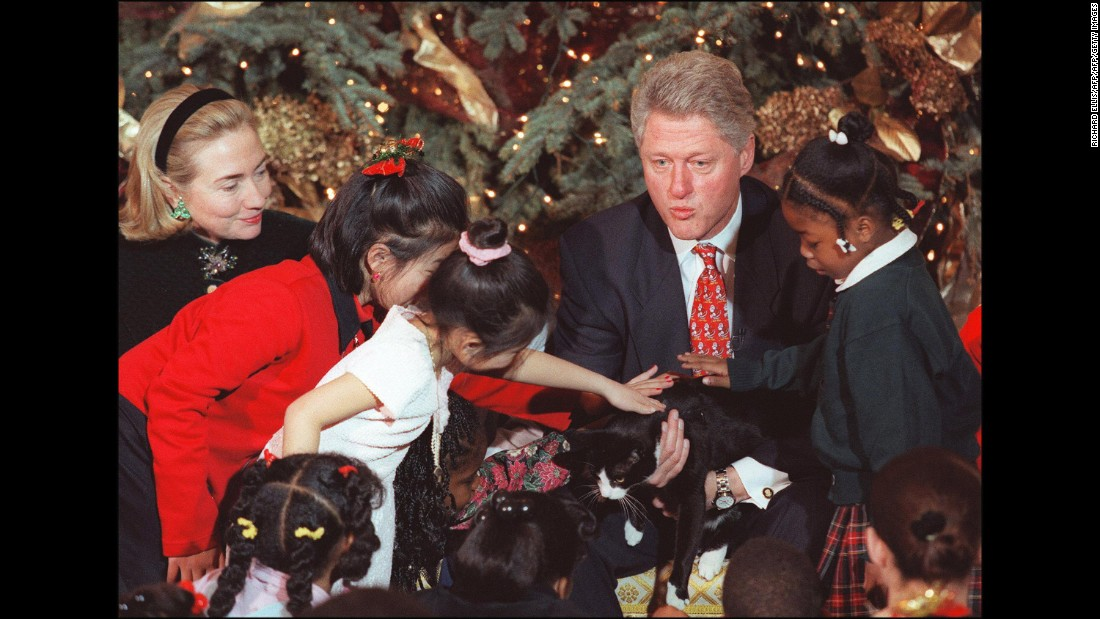 Former President Bill Clinton and First Lady Hillary Clinton, along with Socks, spent time with children during a Christmas gathering at the White House in 1996. <br />