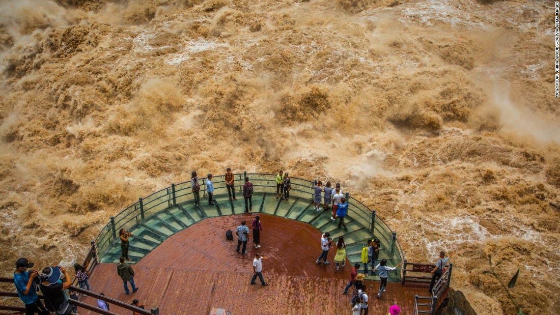 Tourists in China's Yunnan Province watch the flooded Jinsha River at the Tiger Leaping Gorge on Friday, July 15.