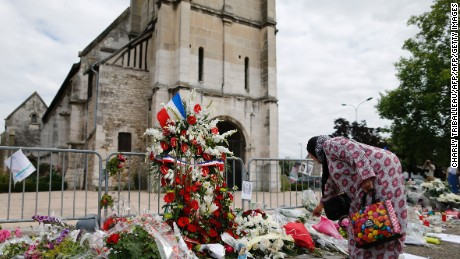 "Muslims put flowers and hold a minute of silence on July 29, 2016 in front of the church if Saint-Etienne-du-Rouvray, western France, where French priest Jacques Hamel waskilled on July 26 in the church during a hostage-taking claimed by Islamic State group, and a call for a mass in his memory on July 29, in front of Jhis house on July 28, 2016 in Saint-Etienne-du-Rouvray, northern France. France's prime minister said on July 29 he would consider a temporary ban on foreign financing of mosques, urging a ""new model"" for relations with Islam after a spate of jihadist attacks. Manuel Valls, under fire for perceived security lapses around the attacks, also admitted a ""failure"" in the fact that one of the jihadists who stormed a church and killed a priest on July 26 had been released with an electronic tag pending trial.  / AFP / CHARLY TRIBALLEAU        (Photo credit should read CHARLY TRIBALLEAU/AFP/Getty Images)"