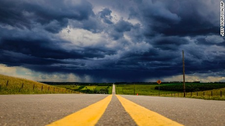 Storm clouds build over a highway in southern Alberta near the town of Carstairs, Canada, Monday, July 4, 2016. Southern and central Alberta have been seeing numerous storm warnings and a few tornado warnings in the last few days as severe thunderstorms capable of producing strong wind gusts, large hail and heavy rain pass through the region. (Jeff McIntosh/The Canadian Press via AP)
