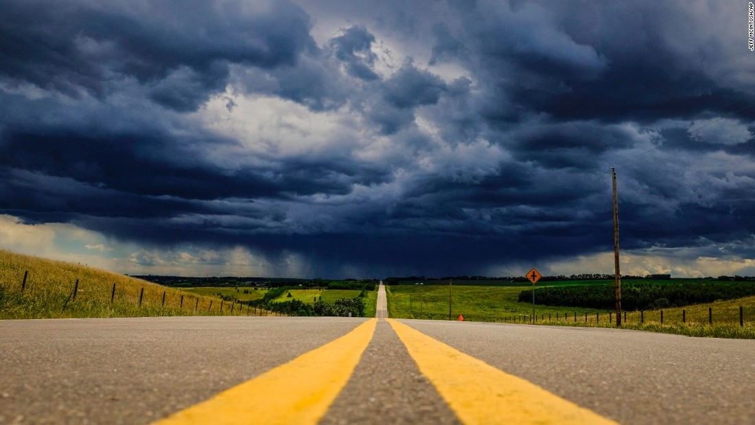 Storm clouds build over a highway in southern Alberta, near the town of Carstairs, on Monday, July 4.