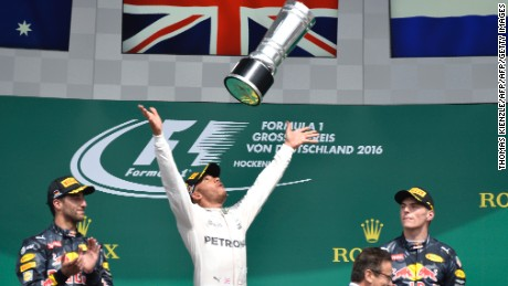 Mercedes AMG Petronas F1 Team's British driver Lewis Hamilton (C) throws the trophy after winning next to second placed Red Bull Racing's Australian driver Daniel Ricciardo (L) amd Red Bull racing's Belgian-Dutch driver Max Verstappen (R) at the Hockenheim circuit, southern Germany, on July 31, 2016 during the Formula One Grand Prix of Germany. / AFP / Thomas Kienzle        (Photo credit should read THOMAS KIENZLE/AFP/Getty Images)