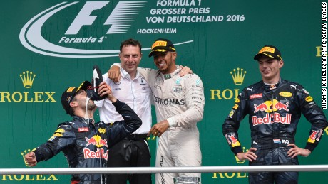 TOPSHOT - Mercedes AMG Petronas F1 Team's British driver Lewis Hamilton (2R) looks at second placed Red Bull Racing's Australian driver Daniel Ricciardo (L) drinking champagne out of a shoe next to Red Bull racing's Belgian-Dutch driver Max Verstappen (R) at the Hockenheim circuit, southern Germany, on July 31, 2016 after the Formula One Grand Prix of Germany. / AFP / Thomas Kienzle        (Photo credit should read THOMAS KIENZLE/AFP/Getty Images)