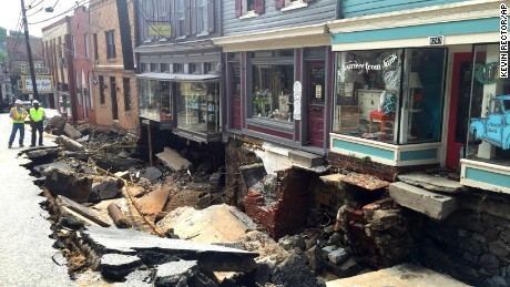 Workers gather on a street damaged by severe flooding in Ellicott City, Maryland.