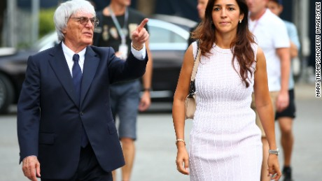F1 chief Bernie Ecclestone walks through the paddock with his wife Fabiana Flosi ahead of the Singapore Formula One Grand Prix in 2014.