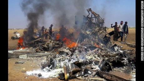 Syrians gather around the burning wreckage of a Russian chopper after it was shot down Monday.