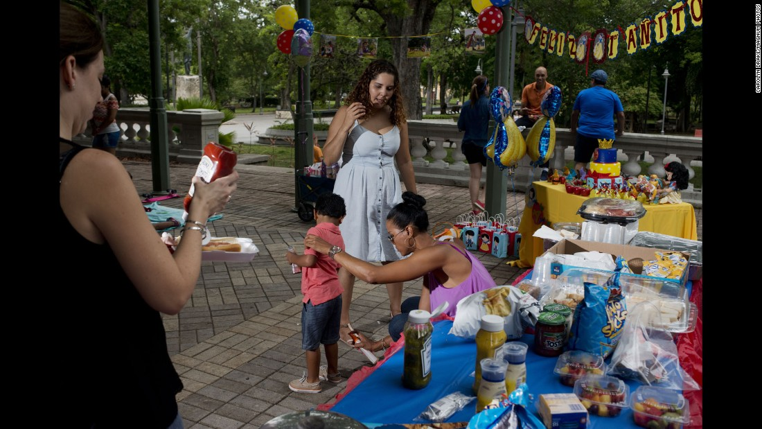 A woman sprays insect repellant on her child at a birthday party in a San Juan park.