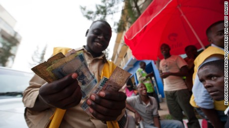 A mobile phone credit seller counts his Rwandan franc currency notes on a street in Kigali.