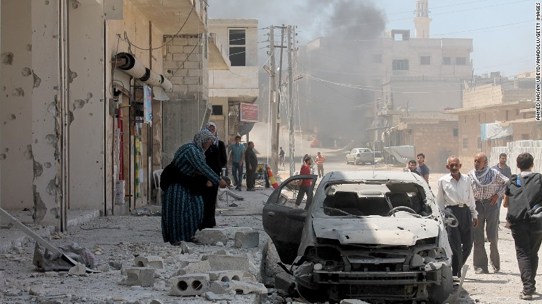 A woman inspects a damaged car after Russian planes carried out an airstrike over Etarib district of Aleppo, Syria.