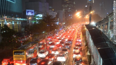 Motorists trespass along the busway lane forcing a bus to use a normal lane, as traffic jams build as the first rains start, during the city's peak rush hour in Jakarta, on November 13, 2015.
