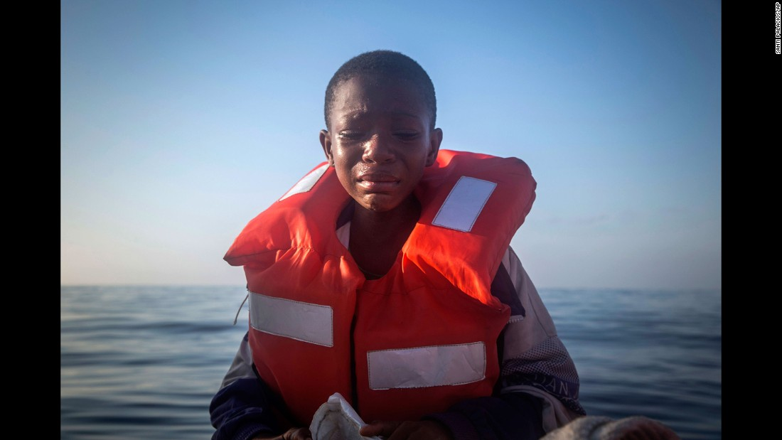 Dustin, an 11-year-old Nigerian refugee, cries aboard a Spanish boat after being rescued from an overcrowded rubber boat in the Mediterranean Sea north of Sabratha, Libya, on Thursday, July 28. Dustin said his mother died in Libya.