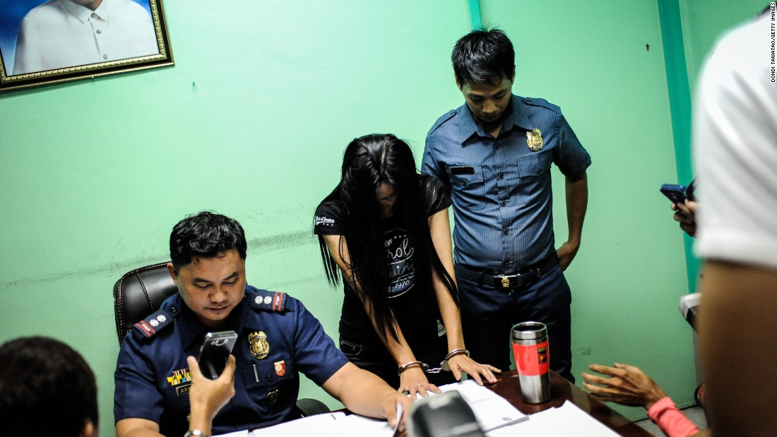 A suspected female member of a drug syndicate is presented by police in Manila on June 22, 2016.