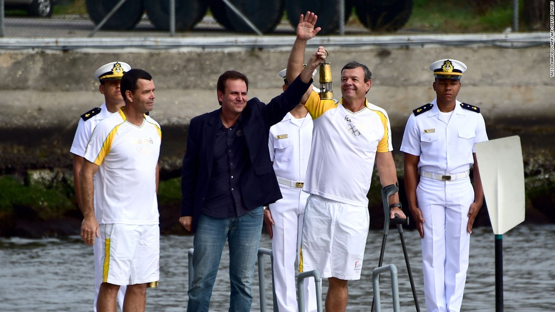 Paes (center) receives the Olympic Torch from Brazilian Olympians Torben Grael and his brother Lars.